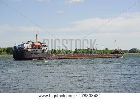 Old bulk carrier on river. Logistic concept