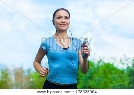 Young athlete running in the park and listens to music in summer morning exercise. Sports and healthy lifestyle.