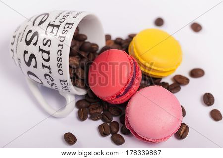 Colorful delicious French macaroons on coffee beans , Cup with coffee beans on white background