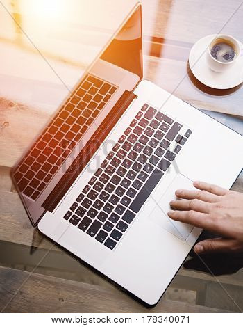 Man working with laptop at sunny office.Male hand pointing on notebook trackpad.Modern notebook, cup of black coffee on the wooden table.Reflections on glass surface.Vertical.Top view.Visual effect