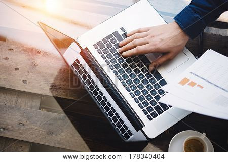 Businessman working at sunny office on laptop while sitting at the wooden table.Man holding paper reports in hands.Reflections on glass surface.Top view.Blurred background.Visual effects