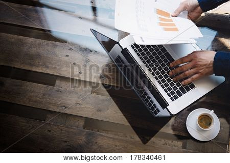 Businessman working at sunny office on laptop while sitting at the wooden table.Man holding paper reports in hands.Reflections on glass surface.Top view.Blurred background
