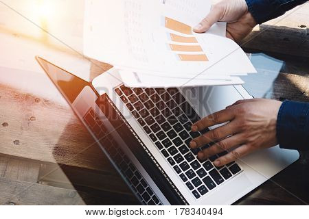 Closeup view of businessman working at sunny office on laptop while sitting at the wooden table.Man holding paper reports in hands.Reflections on glass surface.Top view.Blurred background