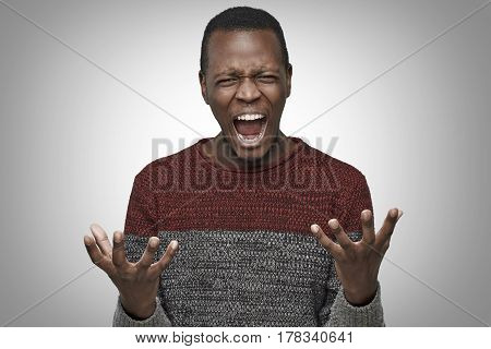 Shut up concept. Mad dark-skinned man shouting with mouth wide open gesturing with hands. Studio portrait of angry and irritated young African American male yelling looking crazy and full of anger