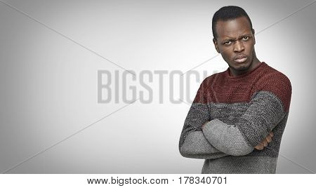Studio portrait of skeptical African American young male in casual sweater looking with suspicious or annoyed expression with hands folded on chest. Copy space for your text or advertising content