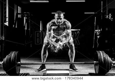 Muscular weightlifter clapping hands and preparing for workout at a gym. Screaming for motivation