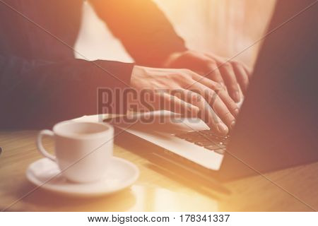 Man in black shirt working with laptop at sunny office.Modern notebook, cup of black coffee and smartphone on the wooden table.Reflections on glass surface.Horizontal, sunlight effect