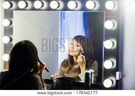 Beautiful Woman Doing Makeup In Front Of A Mirror