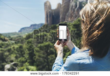Hipster girl making photo on smartphone mobile closeup view tourist hands using gadget phone in travel on background mountains and sky landscape; finger touch screen cellphone mockup nature templates