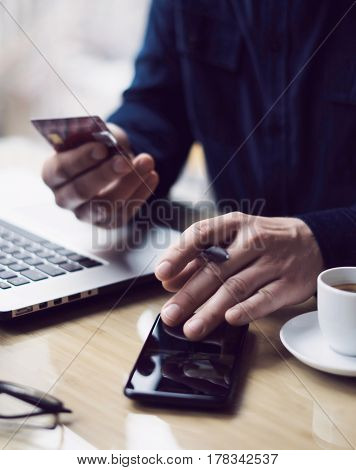 Businessman holding plastic credit card in hand and using smartphone, laptop computer at the wooden table.Man making online payments.Blurred background.Vertical