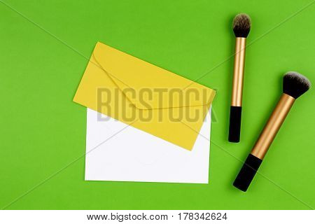 Make up brushes with yellow envelope and white blank card on greenery background. Top view. Flat lay.