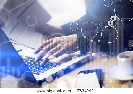 Concept of digital screen, virtual connection icon, diagram, graph interfaces.Businessman working at sunny office on laptop while sitting at the wooden table.Man holding paper documents in hands.Blurred