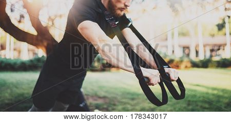 Muscular athlete exercising trx push up outside in sunny park. Fit shirtless male fitness model in crossfit exercise outdoors.Sport fitness man doing push-ups workout.Blurred background.Wide