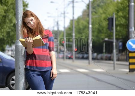 With a book everywhere - Student girl reading a book on the street