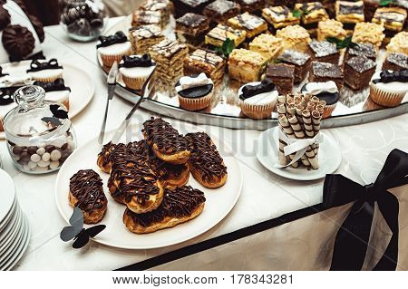 Chocolate pastries on the wedding candybar. Table served for wedding party