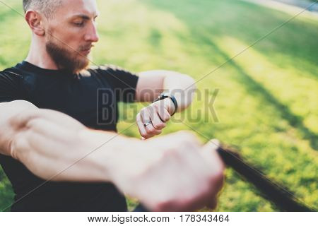 Healthy smart lifestyle concept.Muscular athlete doing great exercising TRX outside in sunny park.Young handsome man in sportswear checking sport tracker watch.Blurred background