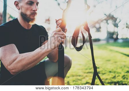 Workout lifestyle concept.Muscular athlete preparing TRX for exercising outside at summer park.Great trx workout sunny morning.Blurred background, flare
