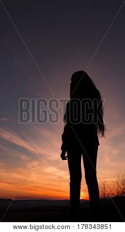 Silhouette of girl before sundown. Happy girl with long hair is standing on the hill with trees.  Breeze is playing with her hair and blowing there. The sky is blue and purple with alpenglow. Girl is looking around.