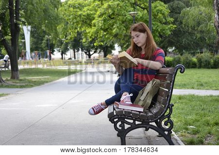 Student girl reading a book on the park bench