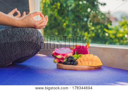 Hand Of A Woman Meditating In A Yoga Pose, Sitting In Lotus With Fruits In Front Of Her Dragon Fruit