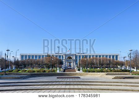 Victory triumphal arch in national assembly squarethe and the government building in chisinau, moldova, blue sky