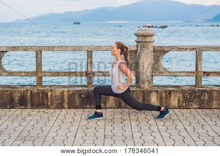 Athletic Girl On Seafront. Young Sportswoman Doing Exercises Against The Sea