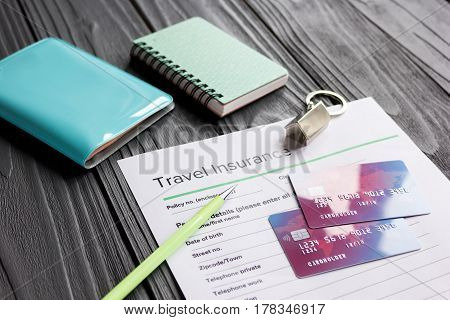 Travel preparation concept with insurance application form and credit cards for online payment on wooden table background