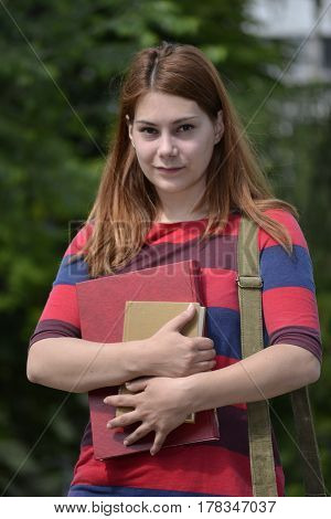 Student girl carries a stack of books in her hands