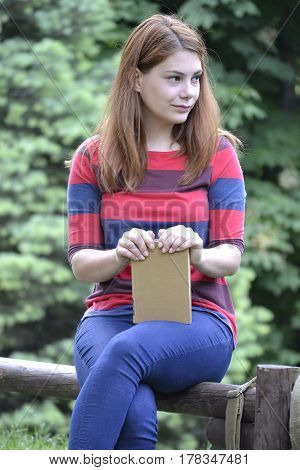 Young student in the park, with books in her hands