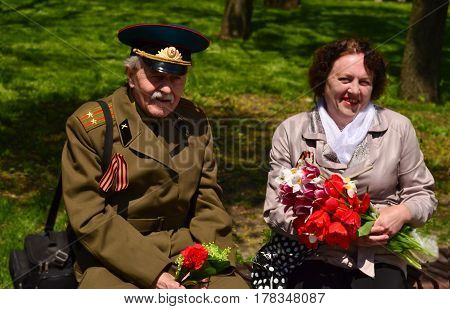 PYATIGORSK RUSSIA - MAY 09 2011: Veterans of Victory Day are sitting on a bench with red tulips