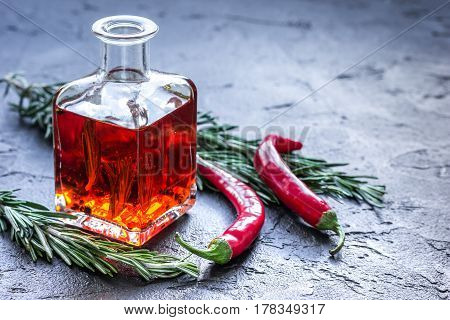 Glass bottle with bright chili oil and herbs on stone table background mock-up