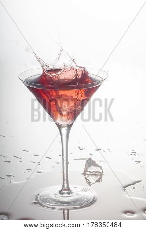 Pink Martini splashed with an ice cube and spilled on white table