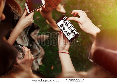 black friday big sale concept text. woman looking on black friday sale text on phone screen and pointing. stylish elegant girls at party celebration in sunny park. advertising