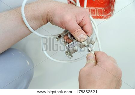 Man's hands inserts a TV antenna cable to a splitter.