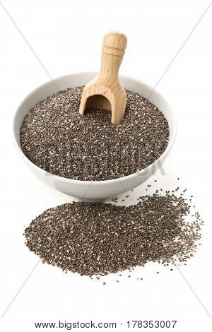 Raw unprocessed dried black chia seeds in white bowl with wooden scoop on white background