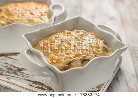Baked gratin casserole chicken with mushrooms in a cream sauce with cheese