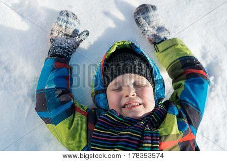 Top view of cute boy lying on snow