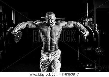 Muscular man training his shoulders with dumbbells in gym