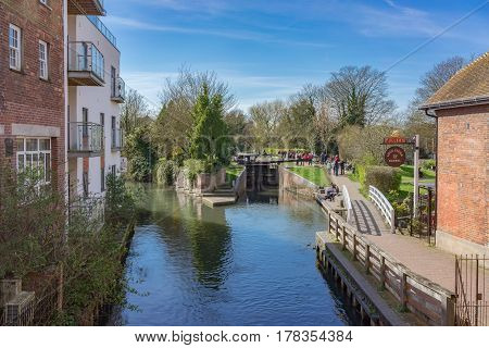 Newbury, UK. 26th March 2017. The River Kennet in central Newbury on a sunny spring day. Some people can be seen in the distance by a lock on the River.