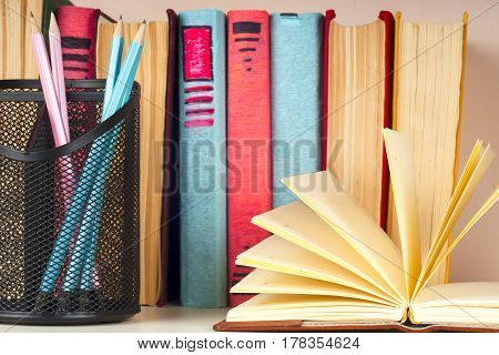 Open book stack of colorful hardback books on light table. Back to school. Copy space for text. Education background. Toned image.