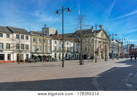 Newbury, UK. 26th March 2017. Market Square in central Newbury on a sunny spring day. The Corn Exchange arts facility can be seen to the right of centre. People are wandering through the streets.