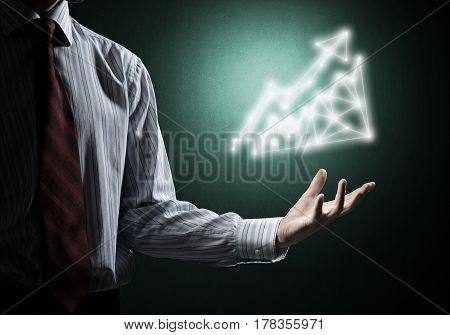 Businessman hand on dark background holding growing graph