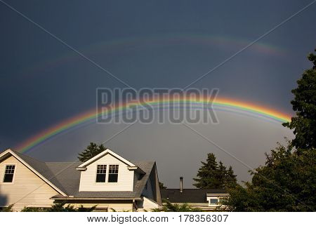 Very vivid main rainbow with duller second rainbow above it over suburban houses