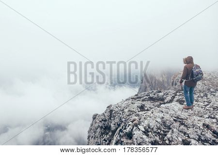 Man with backpack trekking in mountains. Cold weather, fog and clouds. Winter hiking.