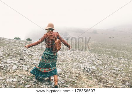 Boho woman wearing hat and leather jacket walking in mountains. Cold weather and fog. Spring or fall hiking. Wanderlust.