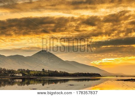 A golden sunset lights up Croagh Patrick, Westport in County Mayo, Ireland.