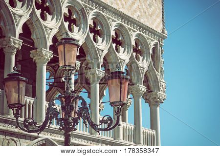 Detail of columns and lamp of the Doge`s palace in Venice (Italy) with blue sky in the background. Edited as a vintage photo with dark edges. Horizontally.