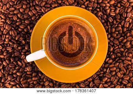 switch on-off symbol on fresh espresso with a beautiful crema and strewn mediumly roasted coffee beans