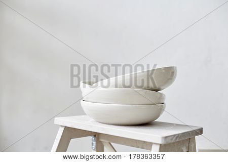 Samples handmade ceramic white plates on wooden table working process in studio