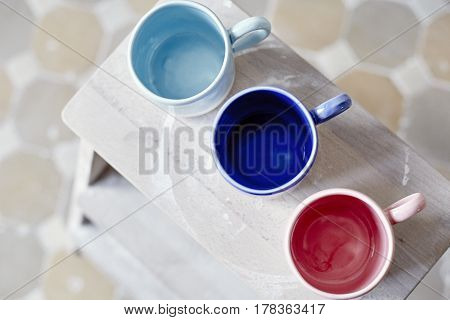 Samples handmade ceramic colored cups on wooden table working process in studio